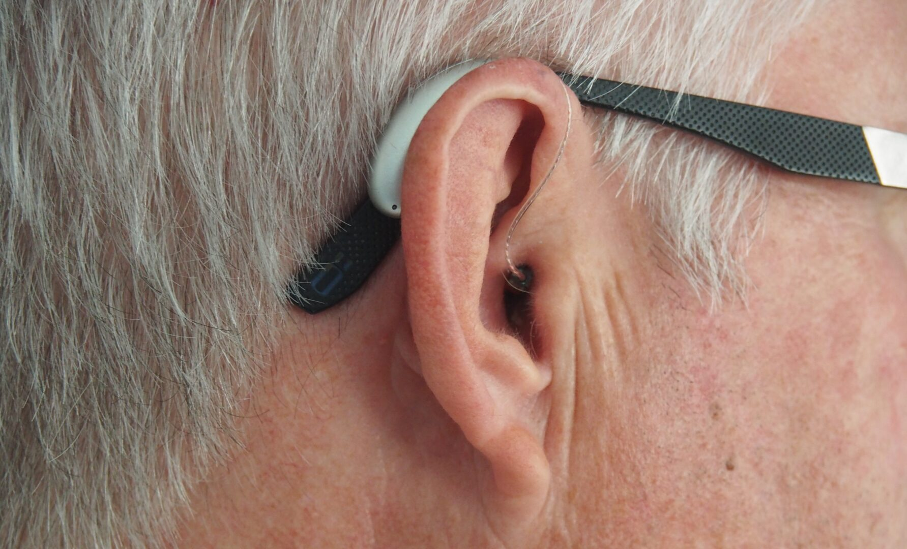 Photo of hearing aid on man's ear
