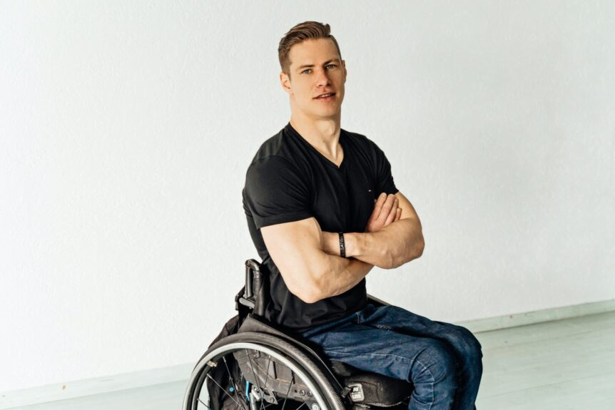 A young man with arms crossed in wheelchair